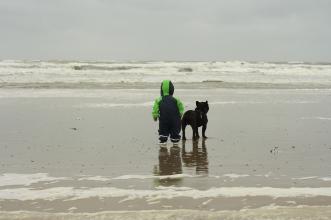 Kind und französische Bulldogge an der Ostsee